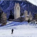 Lone skier passing the old stone church of San Gian inCelerina Switzerland in winter.