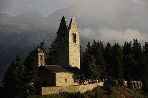 Sun shining on the stone church of San Gian in Celerina Switzerland