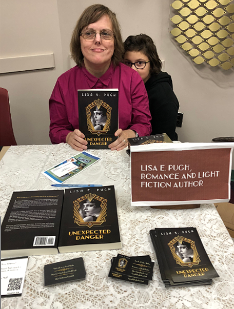 Book fair table with Caitlin photo-bombing